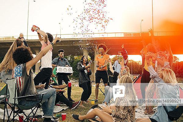 Glückliche Freunde tanzen im Sommer bei einer Musikveranstaltung gegen den Himmel Glückliche Freunde tanzen im Sommer bei einer Musikveranstaltung gegen den Himmel