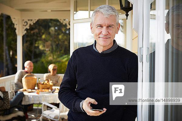 Porträt eines lächelnden reifen Mannes  der auf der Veranda mit Freunden im Hintergrund steht