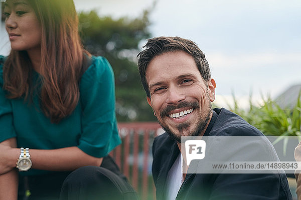 Portrait of smiling bearded man enjoying party with friend on terrace