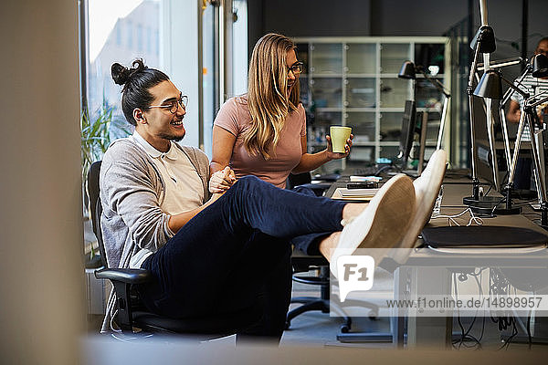 Smiling male and female entrepreneurs looking at laptop in creative office