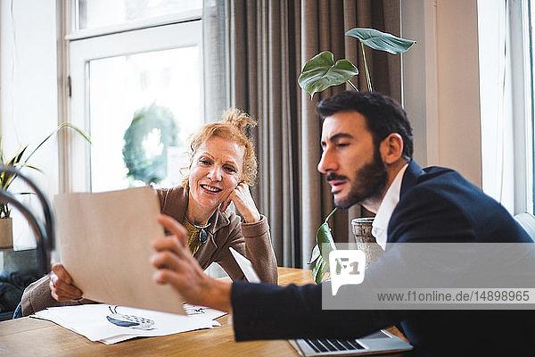Lächelnde Illustratorin zeigt einem männlichen Angestellten im Büro Zeichnung