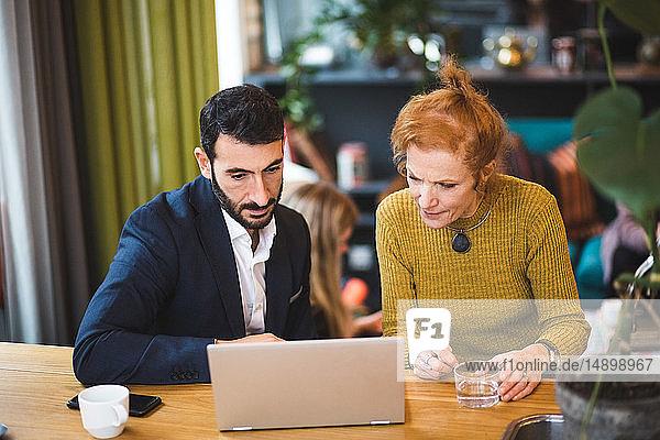 Zuversichtliche männliche und weibliche Geschäftskollegen diskutieren über Laptop am Tisch im Büro
