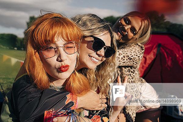 Lächelnde Freunde gestikulieren bei einer Party auf einem Musikfestival