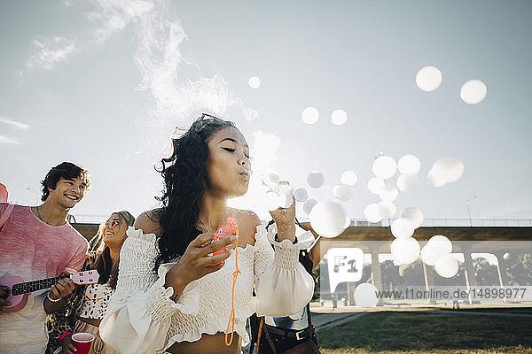 Junge Frau macht Rauchblasen  während sie mit Freunden bei einem Musikkonzert genießt