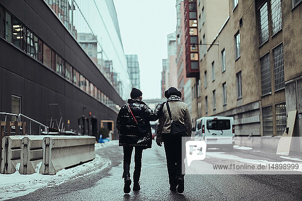 Full length rear view of female friends wearing warm clothing while walking on wet street in city by buildings