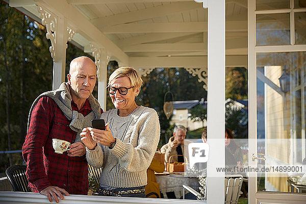 Fröhliche reife Frau zeigt kahlköpfigem Mann mit Freunden im Hintergrund auf der Veranda ihr Handy