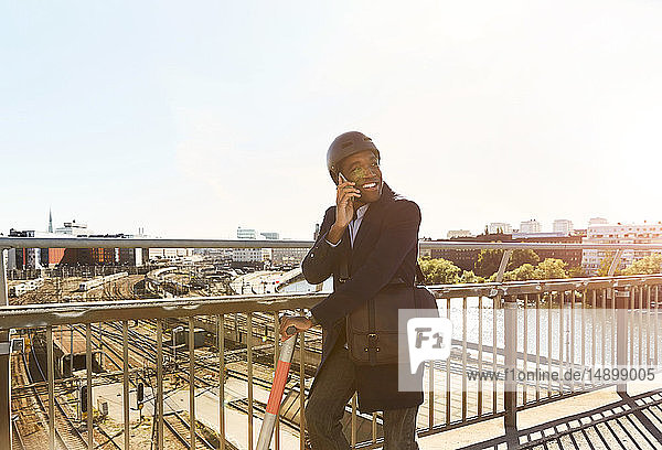 Smiling young man talking on smart phone while standing with electric push scooter at bridge in city against sky