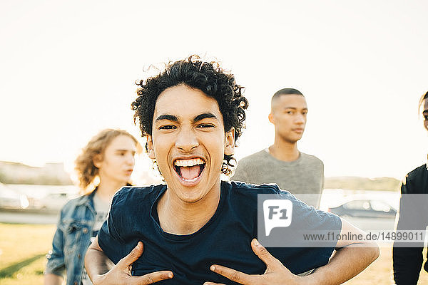 Portrait of happy teenage boy with hands on chest against friends in city