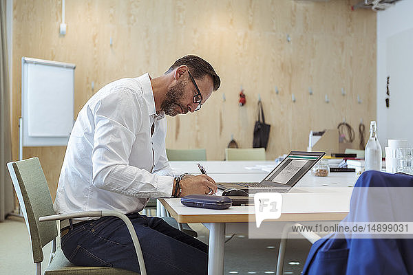 Businessman writing on document while using laptop at table in board room