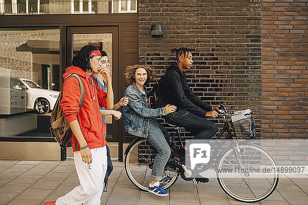 Cheerful young man looking at friends while riding on bicycle in city