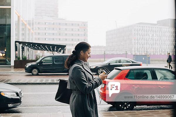 Seitenansicht einer Geschäftsfrau  die ein Smartphone benutzt  während sie auf dem Bürgersteig gegen den Himmel in der Stadt läuft