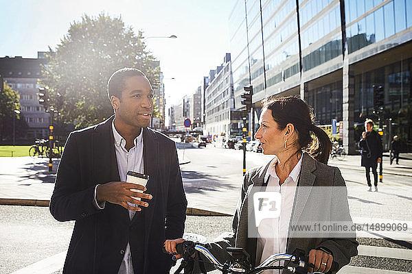 Junger Mann spricht mit reifer Frau  während er gegen Gebäude in der Stadt läuft