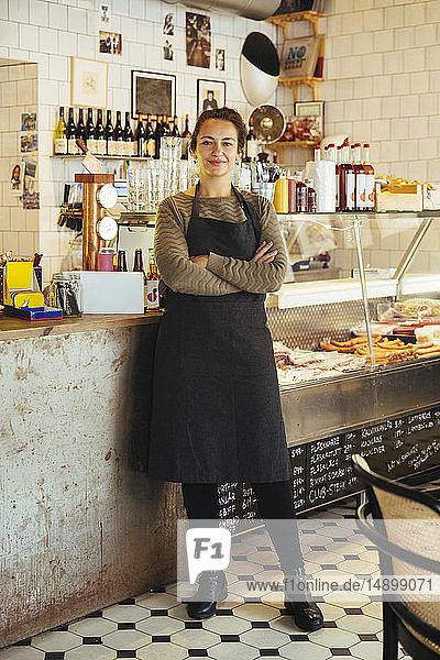 Porträt einer selbstbewussten jungen Besitzerin  die mit verschränkten Armen im Cafe steht