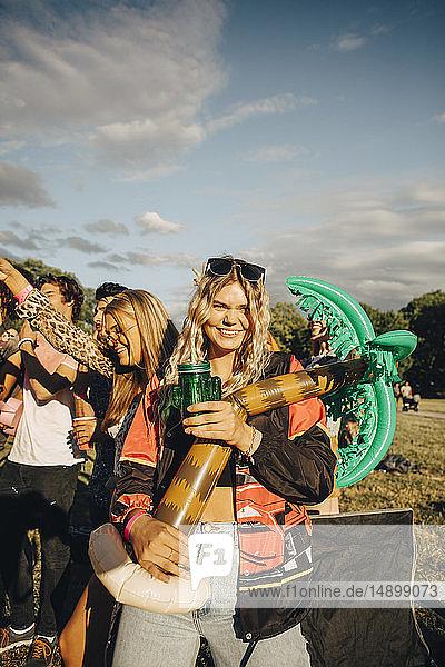 Porträt einer Frau  die einen Ballon hält  während sie sich mit Freunden im Konzert amüsiert