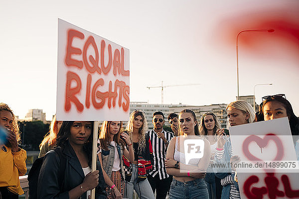 Frauen und Männer mit Plakaten  die für gleiche Rechte gegen den Himmel in der Stadt protestieren