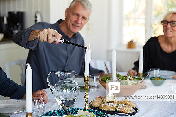 Mature man igniting candle on dining table by friend at home