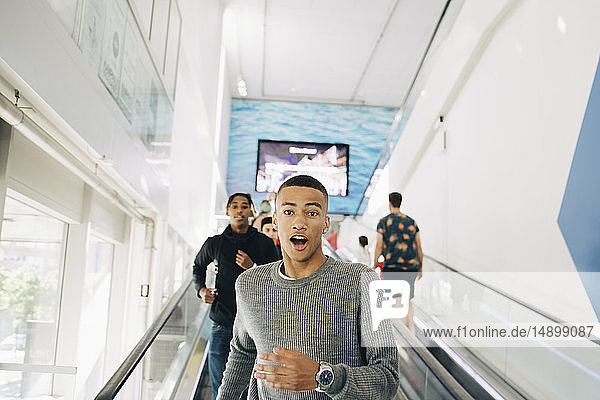 Portrait of shocked teenage boy moving down on escalator with friend in background at shopping mall