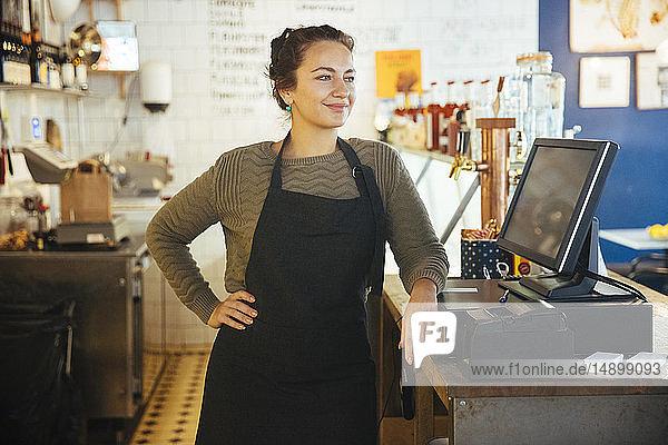 Selbstbewusste junge Besitzerin steht mit der Hand auf der Hüfte an der Kasse an der Kasse im Cafe