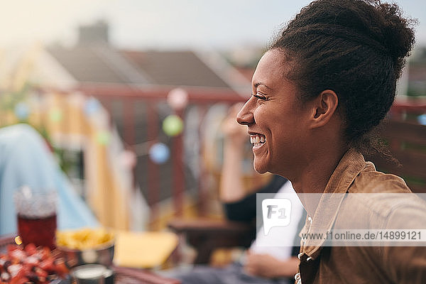 Side view of cheerful young woman enjoying party on terrace
