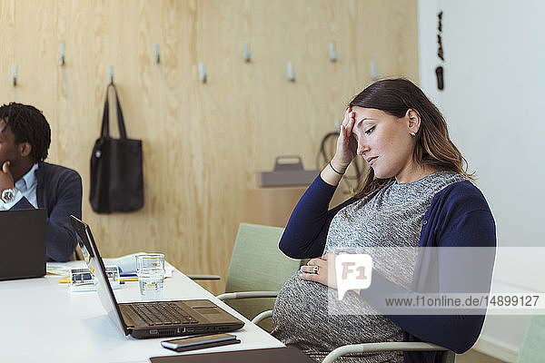 Tired pregnant professional looking at laptop in office meeting