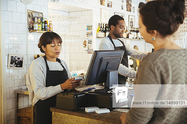 Mature female employee billing customer standing at checkout counter in delicatessen