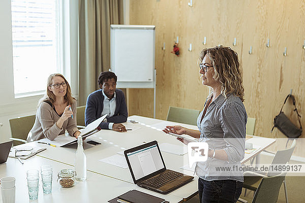 Confident businesswoman discussing with colleagues in meeting at office