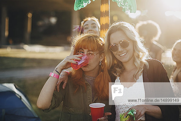 Happy friends enjoying drinks in music event on sunny day