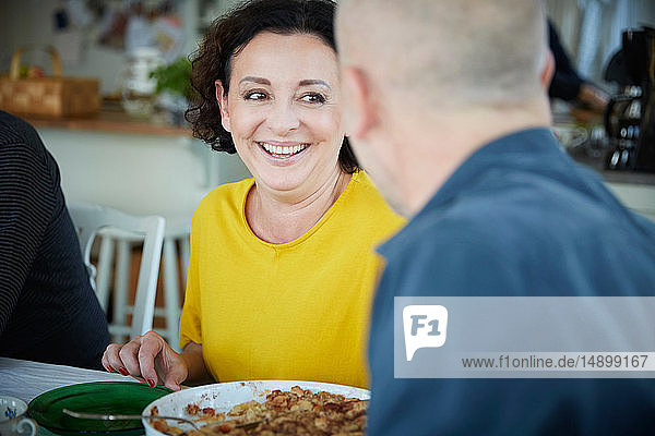 Cheerful mature woman talking with male friend while having lunch at home