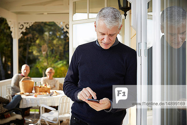 Mature man using mobile phone while standing on porch with friends sitting in background