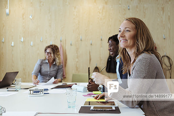 Smiling businesswoman looking away while sitting with colleagues at conference table in board room
