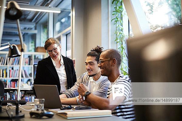 Männliche Unternehmer lächeln  während sie einer Bankmanagerin am Laptop am Schreibtisch im Kreativbüro erklären