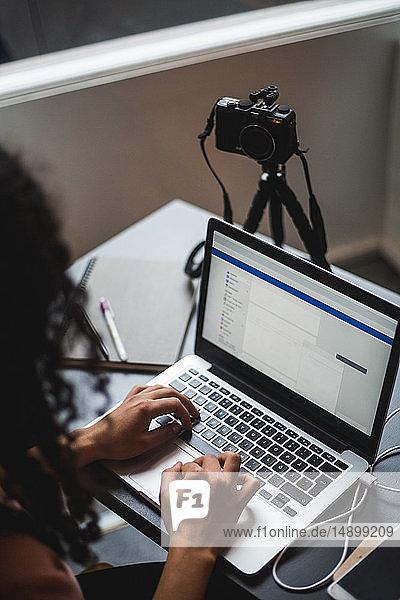 Schrägaufnahme einer jungen einflussreichen Frau  die mit dem Laptop am Schreibtisch im Kreativbüro arbeitet