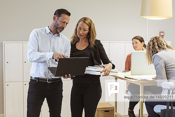 Mature businessman showing laptop to female colleague in board room