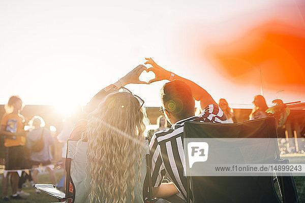 Rückansicht eines Paares  das bei einem Musikfestival an einem sonnigen Tag sein Herz in Form bringt