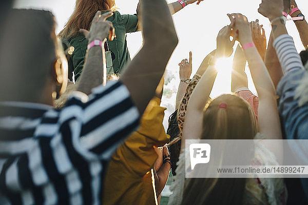 Rückansicht der Menschenmenge mit erhobenen Armen beim Musikfestival
