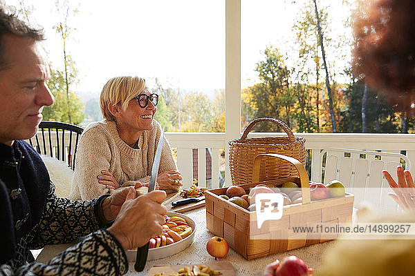Mature man cutting apple while cheerful woman looking away on porch