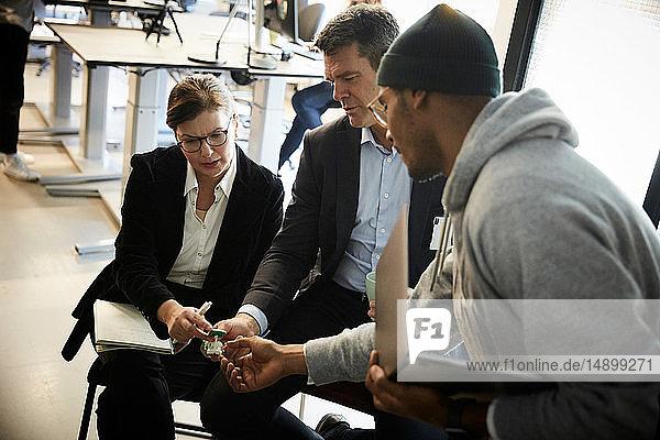 Männlicher Unternehmer zeigt Bankmanagern Solarspielzeugauto bei Besprechung im Kreativbüro