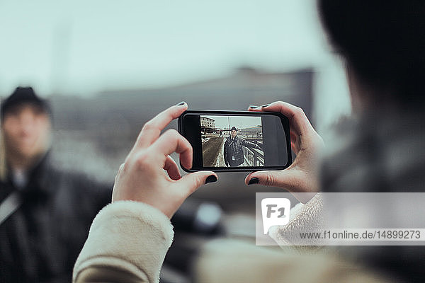 Cropped image of woman photographing friend with smart phone on street in city