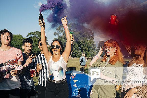 Frau  die während eines Musikkonzerts mit Freunden ein Notfall-Feuer hält