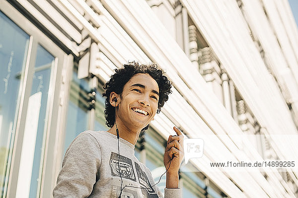 Low angle view of cheerful teenage boy listening music on headphones against building in city