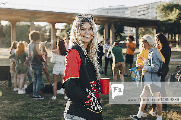 Porträt einer lächelnden Frau mit Getränk  die auf dem Fest gegen Freunde steht