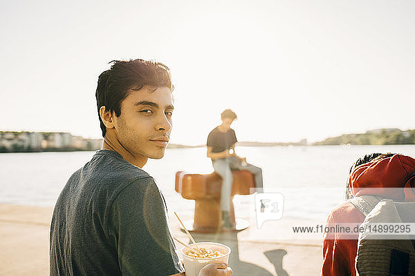 Portrait of young man holding meal in container while sitting on promenade during sunny day