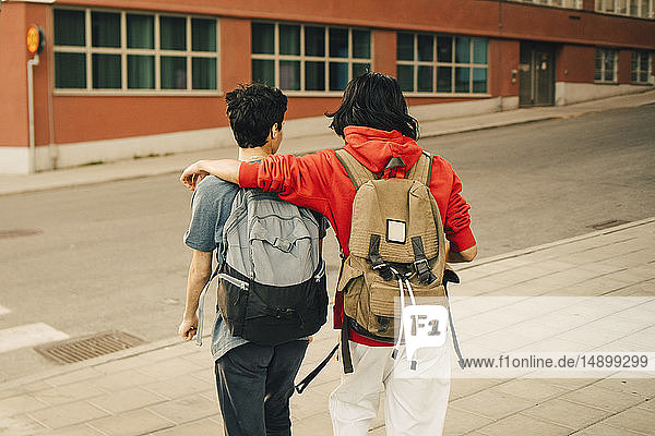 Rear view of friends with backpacks walking on street in city