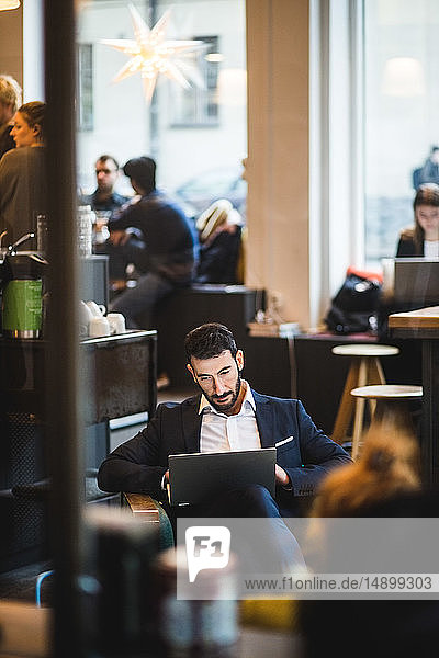 Confident businessman sitting on chair using laptop at creative office