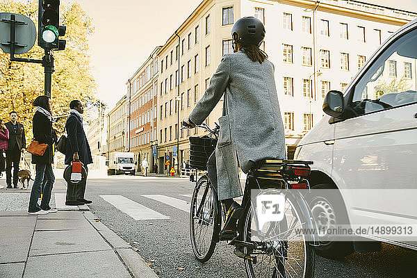 Rear view of woman riding electric bicycle by car on street in city