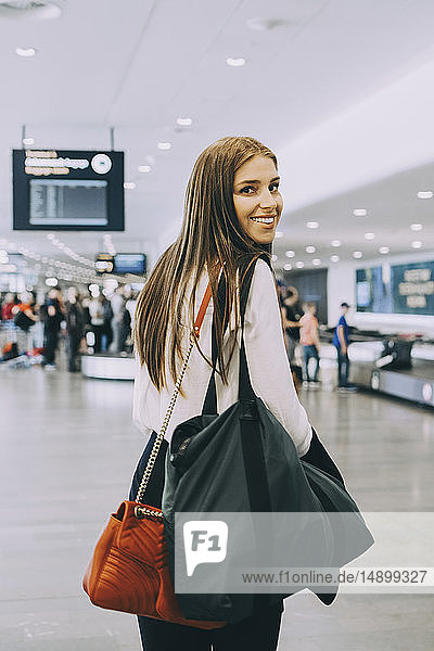 Portrait of smiling young businesswoman walking with colleagues at airport