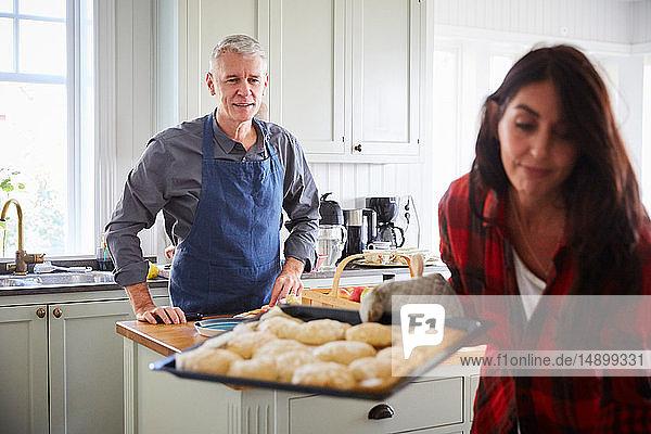 Smiling mature man looking at woman holding baking sheet in kitchen