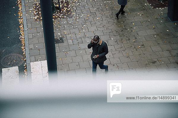 Hochwinkelansicht eines Geschäftsmannes  der ein Smartphone benutzt  während er auf einer Straße in der Stadt läuft
