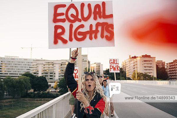 Frauen mit Plakatschreien beim Marschieren für Gleichberechtigung auf der Brücke in der Stadt