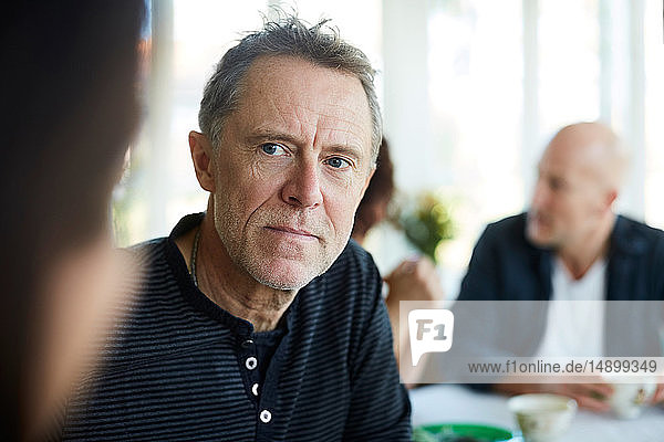 Mature man looking away with friends sitting in background at home